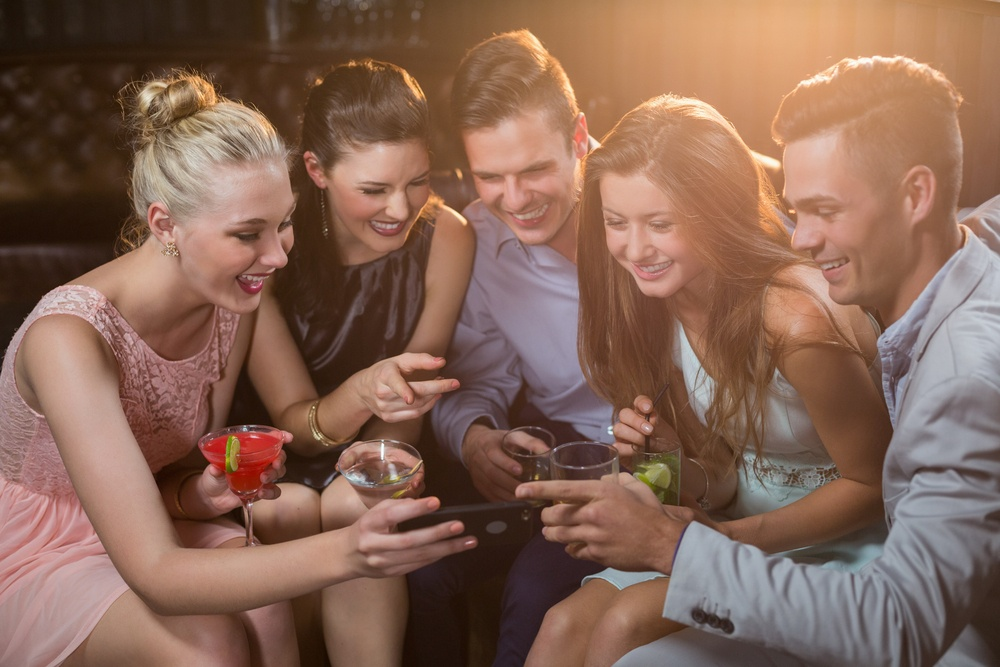 Smiling friends looking at mobile phone while having cocktail in bar.jpeg